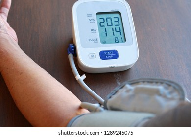 Old Man's health check blood pressure and heart rate at home with digital pressure very high blood pressure test results.Hypertensive urgency.Need some medicine.Health and Medical concept.