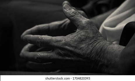 Old man's wrinkled hands in black and white. Close-up image of elderly man's hands touching each other in monochromatic colors.