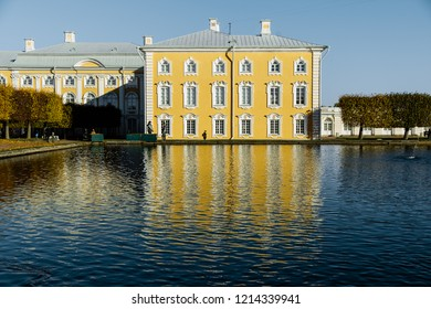 Old mansion by the pond. People walk near the yellow mansion.