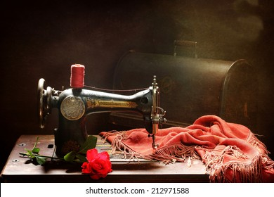 The old manual sewing-machine and bright red rose