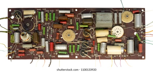 old manually hand-welded chip with a lot of resistors, transistors and wires protruding in different directions.