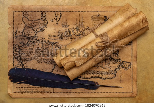 Old map, paper scrolls, raven feather for writing. Vintage image.