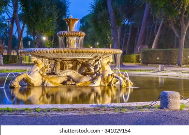 Old marble fountain in the evening in a dark park. Pincio park, Rome (Villa Borghese).
