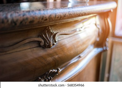 Old marble top drawer. Wood ornament and sunlight. Beautiful antique furniture.