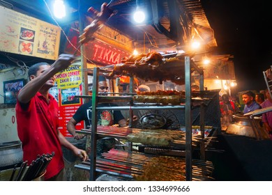 OLD MARKET, NEW DELHI, INDIA - OCTOBER 28 2018 : Spicy chicken seekh kababs are being prepared by men and being stacked on the road side for sale as street food. It is famous for various street foods.