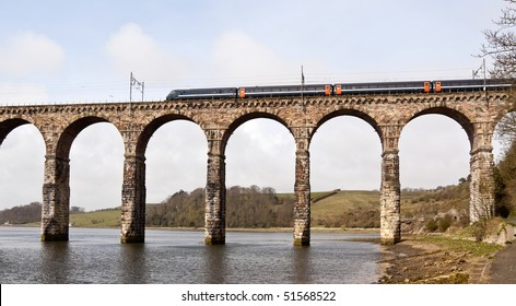 An old masonry arched viaduct carrying a train across the river valley
