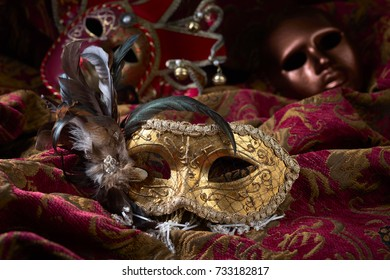 Old masquerade Venetian carnival masks on a dark curtain.