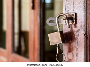 Old master key and keychain hook with steel padlock unlocked on wooden door,Close up and Soft background blur,security for house concept.