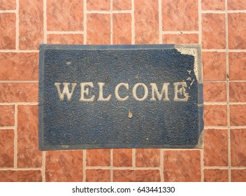 Old mat with welcome text on ceramic tile floor
