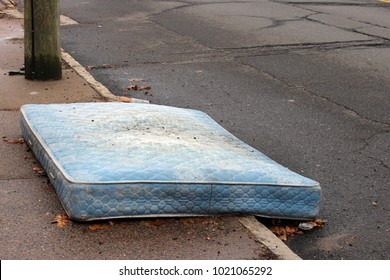 Old mattress sitting outside on curb