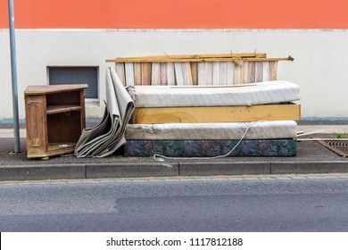 old mattresses, furniture and household items on the roadside