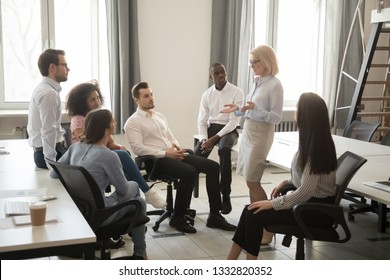 Old mature female leader boss coach training teaching young employees at team business meeting, professional mentor leader speaking explaining strategy at diverse interns group corporate workshop