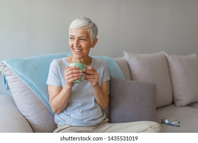 Old mature lady sitting on couch and smiling. She is enjoying tasty drink while relaxing at living room. Copy space. Shot of a mature woman relaxing at home with a cup of coffee while sitting on sofa