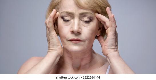 old mature woman portrait face closeup eyes closed hands headake studio shot