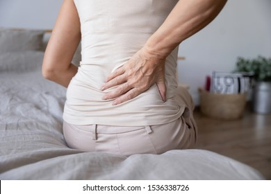 Old mature woman sit on bed touch back feel morning backpain suffer from lower lumbar discomfort muscle pain wake up with backache after sleep on uncomfortable mattress concept, close up rear view