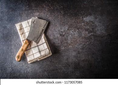 Old meat butcher on dark concrete board.