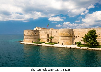 Old medieval Aragonese Castle with palm trees in front of blue sky with white clouds on sea channel in historic center of Taranto city, Puglia (Apulia), Italy