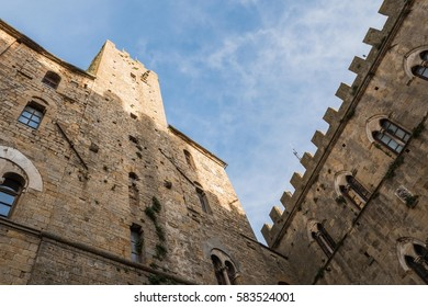 Old medieval buildings, tower and walls on a central square in an historic Renaissance Italian town of Volterra