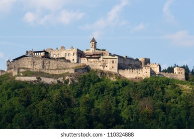 The old medieval castle of Landskron in Villach/Austria located on top of a hill surrounded by a forest.