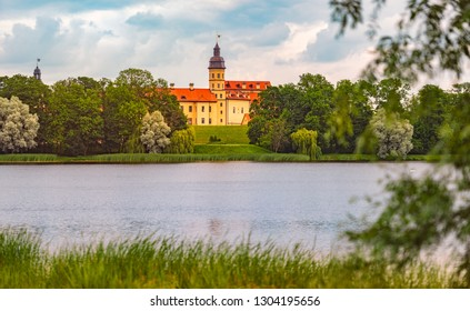 Old medieval castle in Nesvizh, Belarus, Europe. Landmark with blue cloudy sky in background and lake in foreground. Architecture and travel.