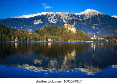 Old medieval castle on the rock against the snowy mountains and the blue sky, Lake Bled, Slovenia