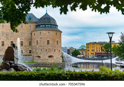 Old medieval castle in Orebro, Sweden, Scandinavia, Europe. Landmark in foreground and blue cloudy sky in background. Architecture and travel.