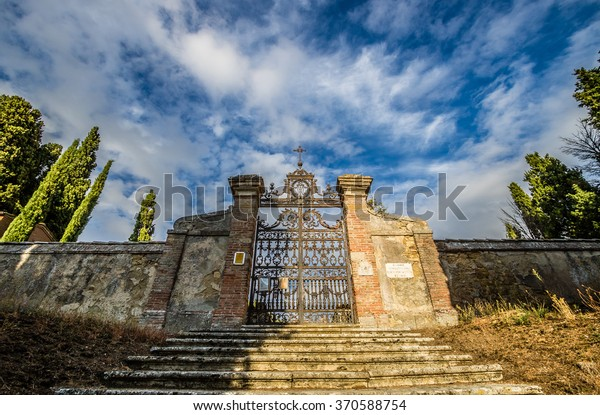Old medieval cemetery gate and red brick wall in Tuscany, Italy