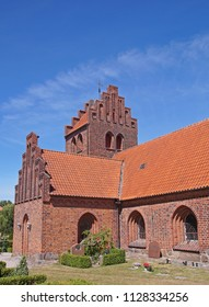 Old medieval Danish church with red bricks seen in a village