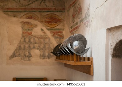 Old medieval metal helmets of the Italian knights on the shelf in the fortress (Castle) of Brescia, Lombardy, Italy. The element of armour to protect the head of the soldier (warrior).