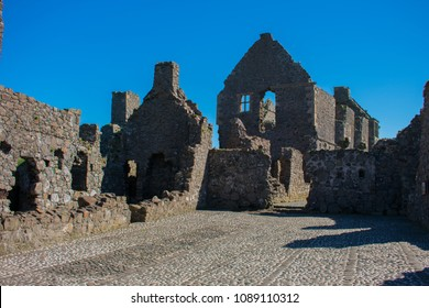 old medieval ruins of Dunluce castle in northern ireland against clear blue sky