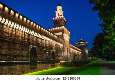 Old medieval Sforza Castle Castello Sforzesco lightning facade, walls, tower La torre del Filarete with lights, trees at sunset, dusk, twilight, evening, blue sky background, Milan, Lombardy, Italy