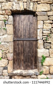 Old medieval wooden door in a stone wall