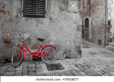 Old Mediterranean town street with red retro bike and sunlight - vintage toned, Italy, Europe