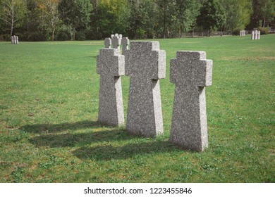 old memorial stone crosses placed in row at graveyard