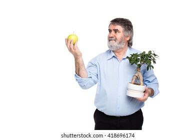 old men with gray beard holding a small tree and green apple in in hands, isolated on white