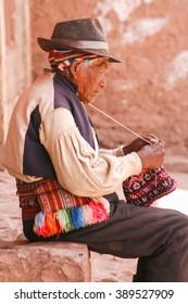 Old men knitting at taquile island in puno peru.