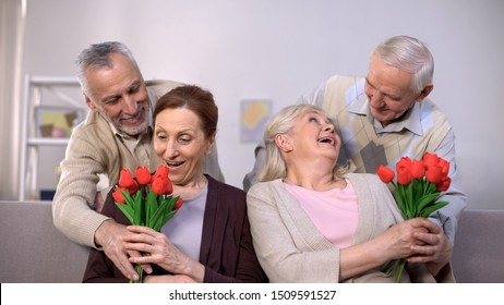 Old men presenting bunches of tulips to beloved ladies, international women day