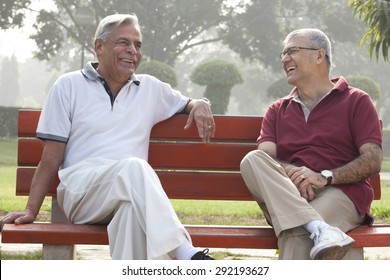Old men sitting on a bench in a park laughing