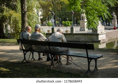 Old men sitting on a wooden bench in park and talking to each other