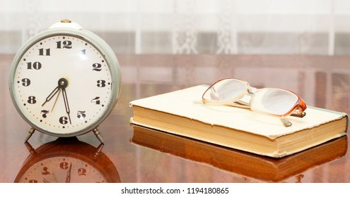 old metal alarm clock, glasses, a book on an old table near the window