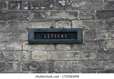 An old metal black letterbox with sign Letters on old grey brick stone wall. British  old classic building detail. Communication concept