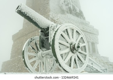 An old metal cannon. The cannon participated in the battles of liberation of Bulgaria in 1877. Winter fog, lots of snow, old cannons covered with snow.