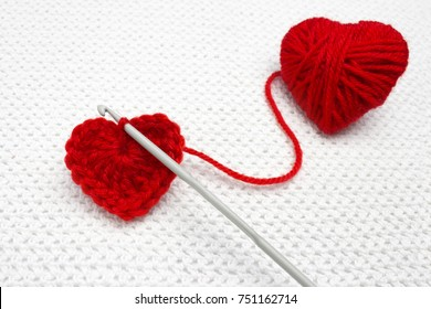 Old metal crocheting hook and red yarn ball like a heart on the white crochet background. A handmade crocheted wool organic red heart. Red heart made of wool yarn and crochet heart. Soft focus