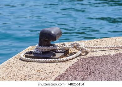 Old metal dock mooring pole with ring and rope for securing fishing boats .