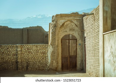 Old metal door in a brick wall of the old city of Kashan, Iran. In the background clay ancient walls, wires and mountains