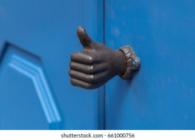 Old metal door handle in a form of a hand with thumb up