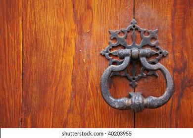 Old metal door handle knocker on wooden background