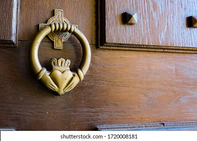 Old metal door-knocker, sculpted according to the traditional representation of an Irish Claddagh ring :  two clasped hands (symbol of friendship) holding a heart (love) topped by a crown (loyalty)