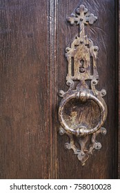 Old metal lock knocker, with a christian cross, on a door of wood