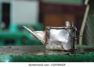 Old metal oil can on workbench background.